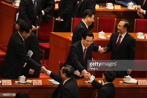 China's Communist Party Chief Xi Jinping shakes hands with China's Premier Wen Jiabao as China's President Hu Jintao shakes hands with delegate Ling...