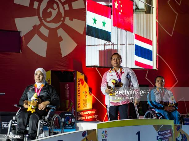 China's Cui Jianjin Syria's Fatema Alhasan and Thailand's Anon Somkhoun observe the national anthem at the podium after winning gold silver and...