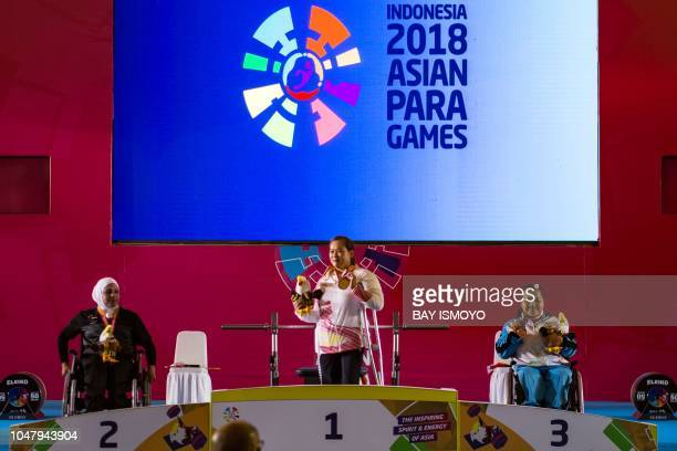 China's Cui Jianjin Syria's Fatema Alhasan and Thailand's Anon Somkhoun look on from the podium after winning gold silver and bronze respectively...