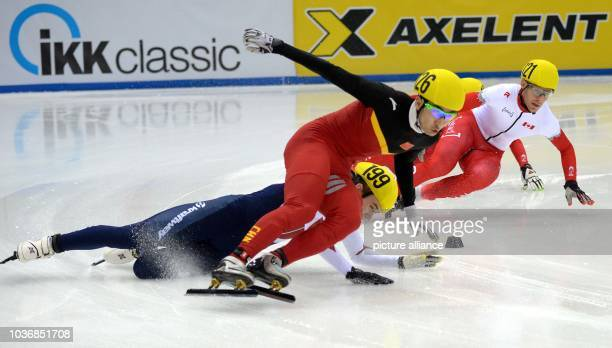 China's Dajing Wu falls with Russia's Dmitry Migunov during the 500m at the Short Track World Cup quarterfinals in the EnergieVerbund Arena in...