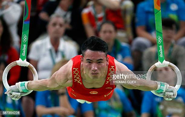 TOPSHOT China's Deng Shudi competes in the rings event of the men's team final of the Artistic Gymnastics at the Olympic Arena during the Rio 2016...