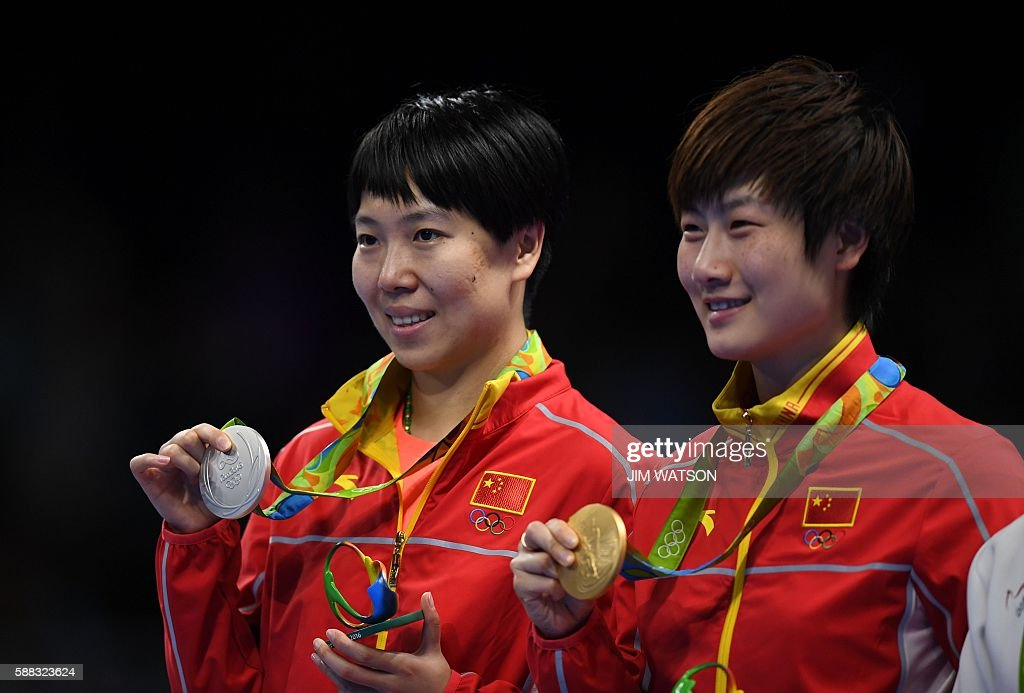 China's Ding Ning and her compatriot China's Li Xiaoxia pose with their gold and silver medals after Ding won their women's singles final table tennis match at the Riocentro venue during the Rio 2016 Olympic Games in Rio de Janeiro on August 10, 2016. / AFP / Jim WATSON