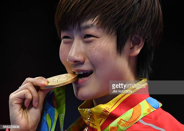 China's Ding Ning bites her gold medal after beating China's Li Xiaoxia in their women's singles final table tennis match at the Riocentro venue...