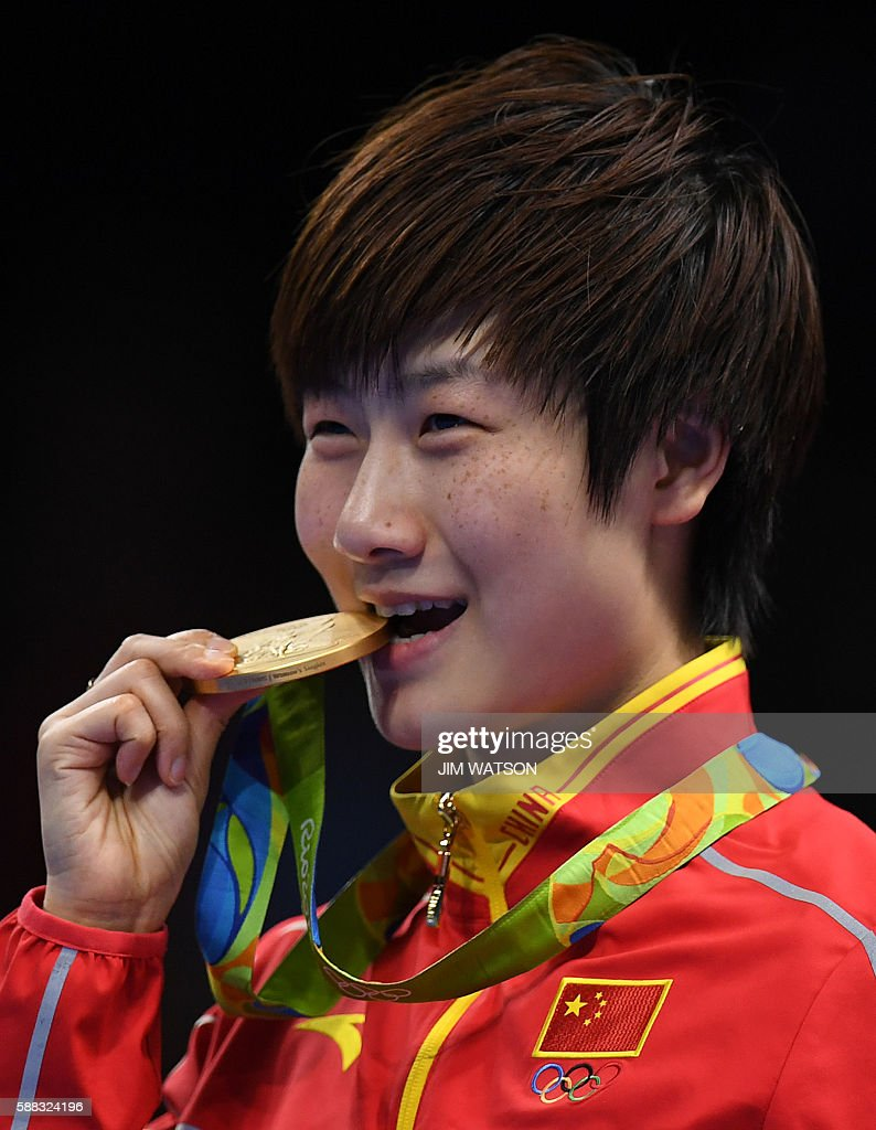 China's Ding Ning bites her gold medal after beating China's Li Xiaoxia in their women's singles final table tennis match at the Riocentro venue during the Rio 2016 Olympic Games in Rio de Janeiro on August 10, 2016. / AFP / Jim WATSON