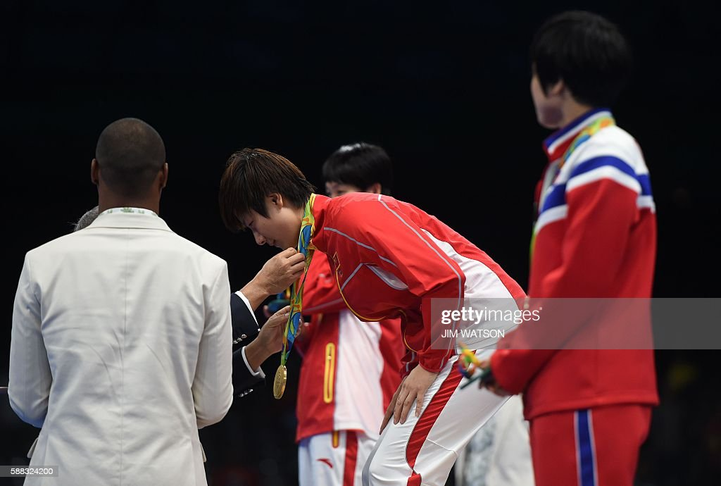 China's Ding Ning (C) gets her gold medal after beating China's Li Xiaoxia in their women's singles final table tennis match at the Riocentro venue during the Rio 2016 Olympic Games in Rio de Janeiro on August 10, 2016. / AFP / Jim WATSON