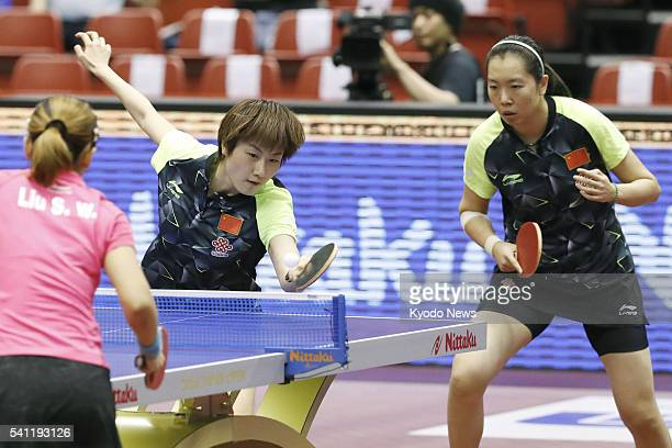 China's Ding Ning hits a shot as partner Li Xiaoxia looks on during the women's doubles final of the International Table Tennis Federation World Tour...
