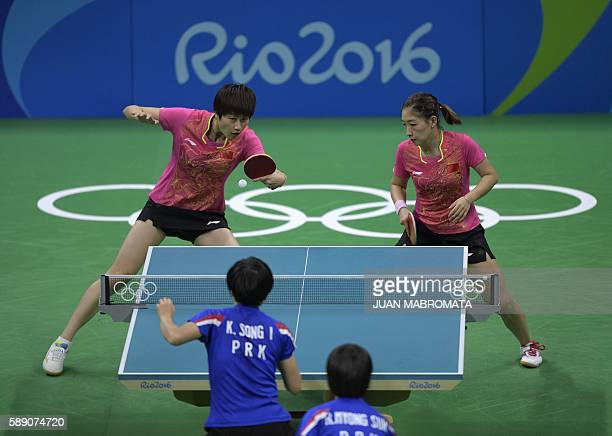 China's Ding Ning hits a shot next to China's Liu Shiwen in their women's team quarterfinal table tennis match against North Korea's Ri Myong Sun and...