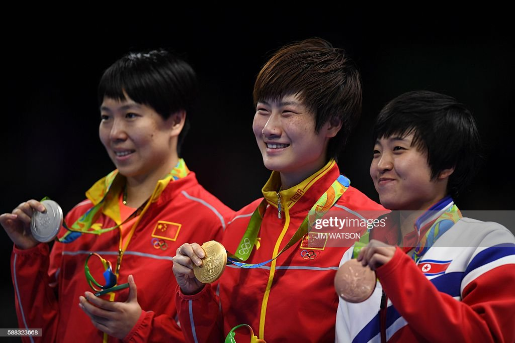 China's Ding Ning (C) with her gold medal, her compatriot Li Xiaoxia (L) with the silver medal and North Korea's Kim Song I with the bronze medal pose after the women's singles final table tennis match at the Riocentro venue during the Rio 2016 Olympic Games in Rio de Janeiro on August 10, 2016. / AFP / Jim WATSON