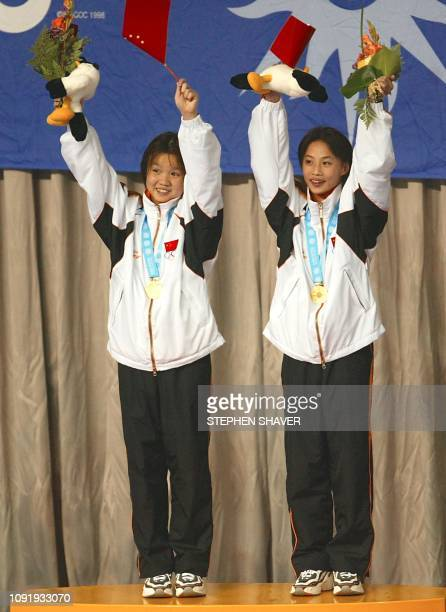 China's Duan Qing and Li Ting celebrate after receiving the team gold medal after performing in the women's synchronized diving finals 09 October...