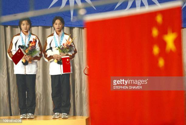 China's Duan QIng and Li ting stand on a the award podium while listening to the Chinese national anthem after winning the team gold medal in the...