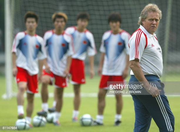China's Dutch coach Arie Haan watches as his players go through their last training session 06 August 2004 in Beijing one day before their Asian Cup...