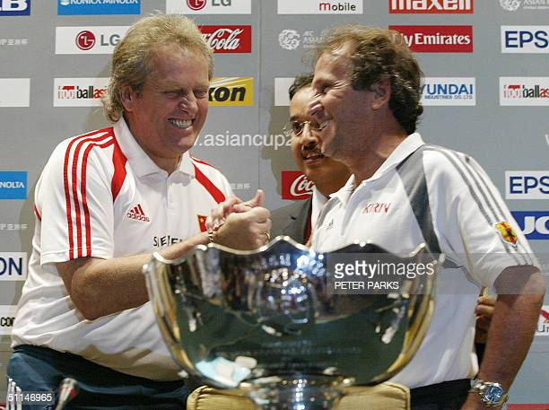 China's Dutch soccer coach Ari Haan shakes hands with Japan's Brazilian coach Zico with the Asia Cup in the foreground at a press conference in...