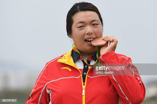 China's Feng Shanshan poses with her bronze medal on the podium of the Women's individual stroke play at the Olympic Golf course during the Rio 2016...