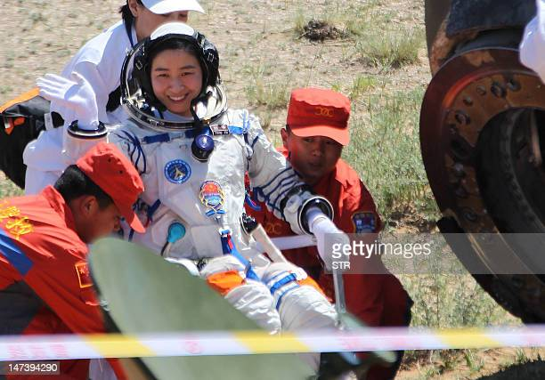 China's first female astronaut 33yearold Liu Yang gets carried by two retrieval crew members after she emerged from the charred return capsule of the...