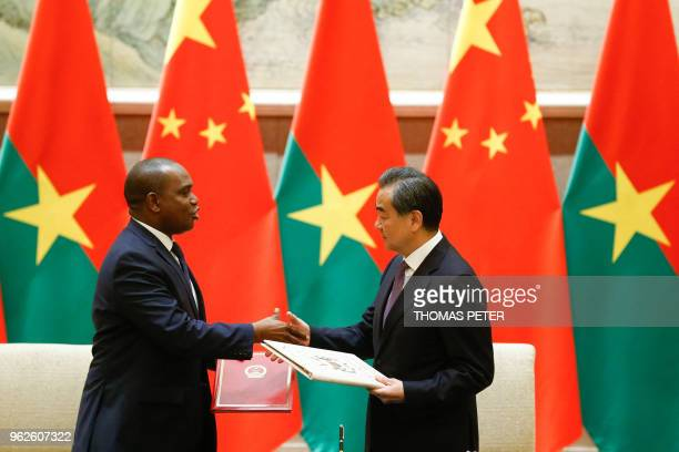 China's Foreign Minister Wang Yi and Burkina Faso's Foreign Minister Alpha Barry shake hands as they attend a signing ceremony establishing...