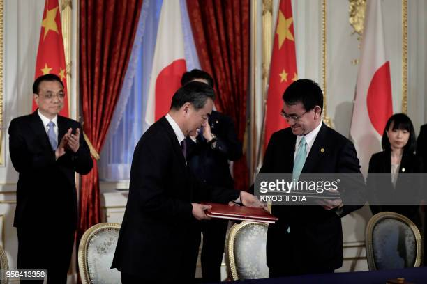 China's Foreign Minister Wang Yi and Japan's Foreign Minister Taro Kono exchange signed documents while China's Premier Li Keqiang and Japan's Prime...