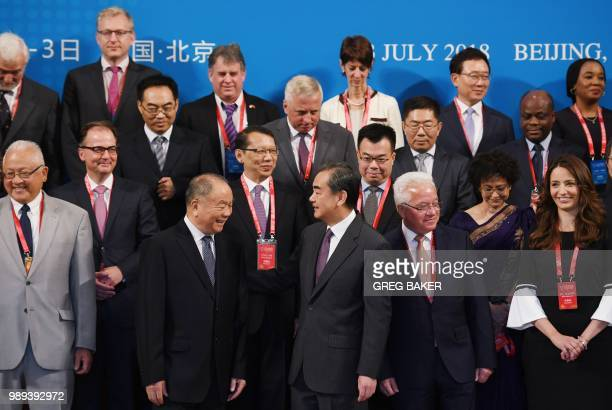 China's Foreign Minister Wang Yi chats with Wang Lequan president of the China Law Society and foreign delegates after a group photo before the...