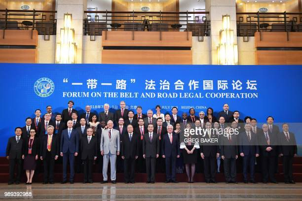 China's Foreign Minister Wang Yi poses for a photo with foreign delegates before the opening session of the Belt and Road Forum on Legal Cooperation...