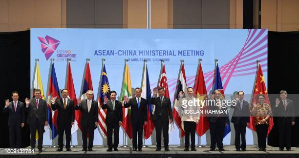 China's Foreign Minister Wang Yi poses with Laos' Minister of Foreign Affairs Saleumxay Kommasith Malaysia's Foreign Minister Saifuddin Abdullah...