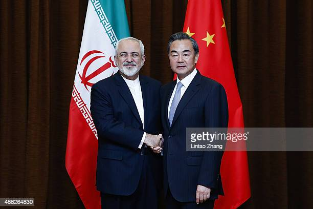 China's Foreign Minister Wang Yi shakes hands with Iranian Foreign Minister Javad Zarif before a bilateral meeting on September 15 2015 in Beijing...