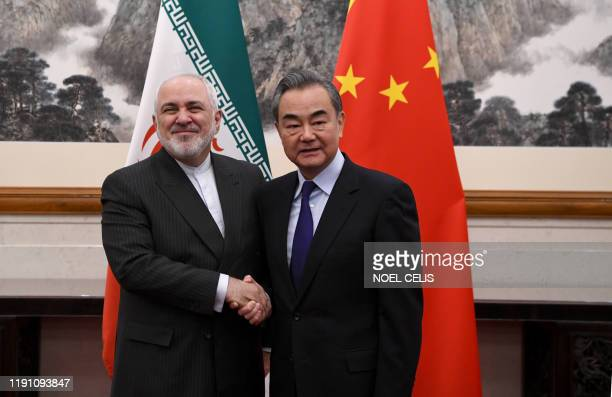 China's Foreign Minister Wang Yi shakes hands with Iran's Foreign Minister Mohammad Javad Zarif during their meeting at the Diaoyutai State Guest...