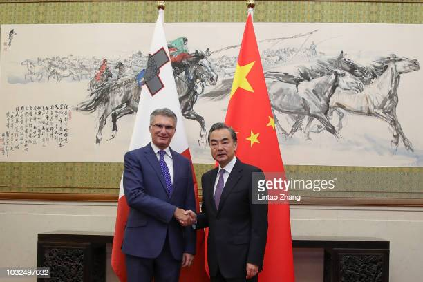 China's Foreign Minister Wang Yi shakes hands with Malta's Minister of Foreign Affairs Carmelo Abela at Diaoyutai State Guesthouse on September 13...