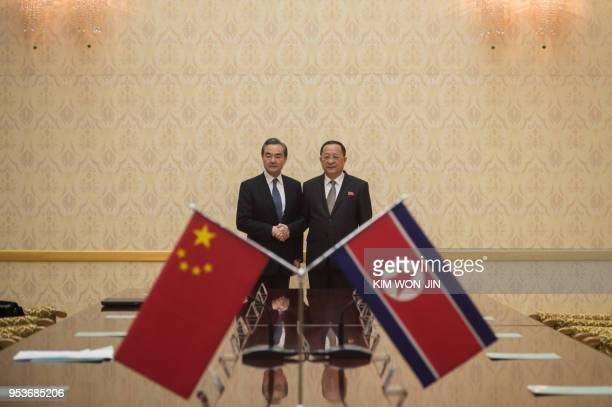TOPSHOT China's foreign minister Wang Yi shakes hands with North Korea's foreign Minister Ri Yong Ho at the Mansudae Assembly Hall in Pyongyang on...