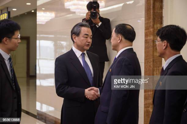 China's foreign minister Wang Yi shakes hands with North Korea's vice foreign minister Ri Kil Song after arriving at Pyongyang international airport...