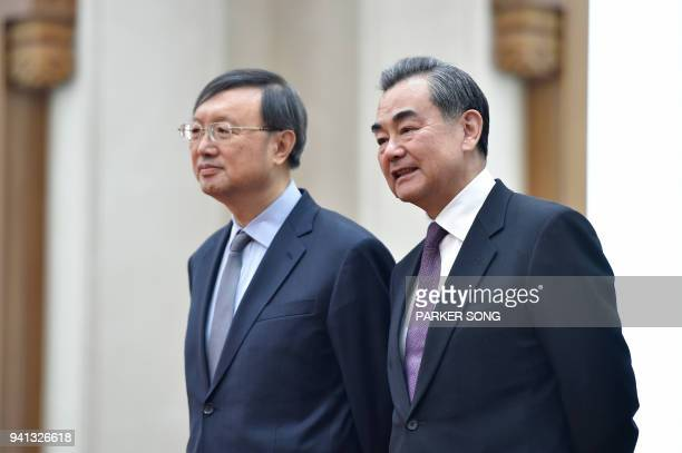 China's Foreign Minister Wang Yi talks with China's State Councillor Yang Jiechi before a signing ceremony between Zimbabwe and China at the Great...