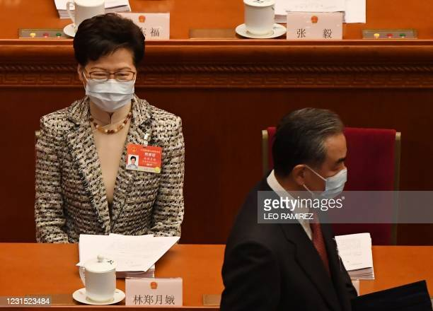 China's Foreign Minister Wang Yi walks past Hong Kong's Chief Executive Carrie Lam as he arrives for the opening ceremony of the National People's...