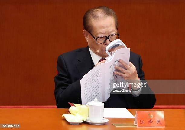 China's former president Jiang Zemin reads a document while he attends the opening session of the Chinese Communist Party's Congress at the Great...