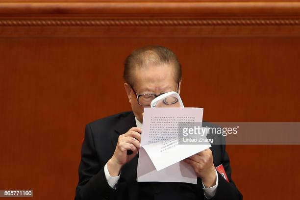 China's former president Jiang Zemin reads the file with a magnifying glass during the closing of the 19th Communist Party Congress at the Great Hall...