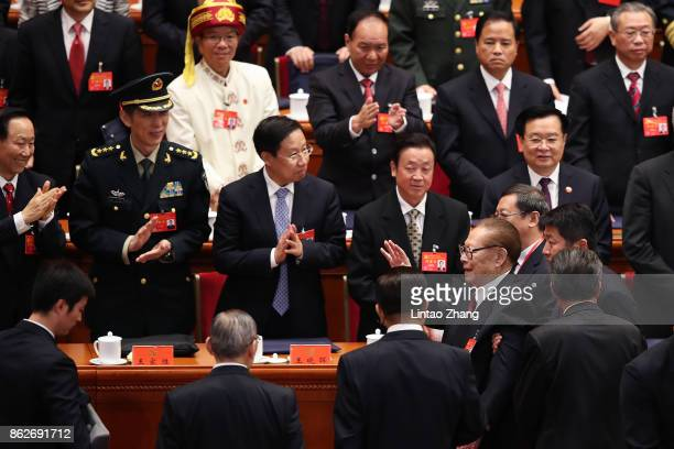 China's former president Jiang Zemin waves as he leaves after the opening session of the Chinese Communist Party's Congress at the Great Hall of the...