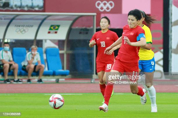 China's forward Wang Shanshan runs with the ball during the Tokyo 2020 Olympic Games women's group F first round football match between China and...
