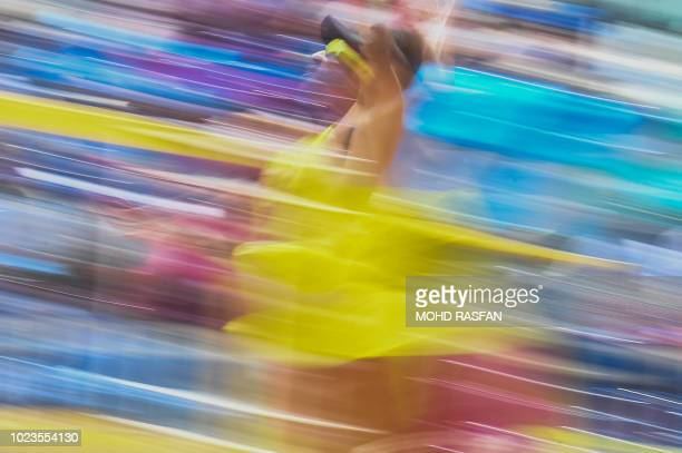 China's Gao Peng spikes the ball against Qatar in their men's beach volleyball semifinal during the 2018 Asian Games in Palembang on August 26 2018