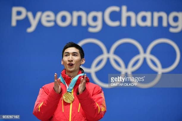 China's gold medallist Wu Dajing claps on the podium during the medal ceremony for the short track Men's 500m at the Pyeongchang Medals Plaza during...