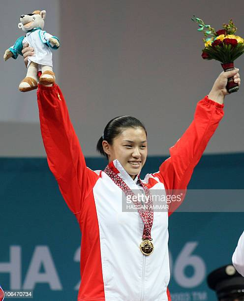 China's gold winner Cao Lei stands on the winner's podium at the end of the 75kg category in women's weightlifting at the 15th Asian Games in Doha 05...