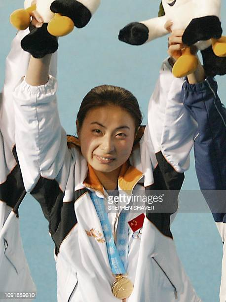 China's Guo Jingjing celebrates after winning the gold medal during an awards ceremony for the women's 3metre springboard final 10 October 2002 at...