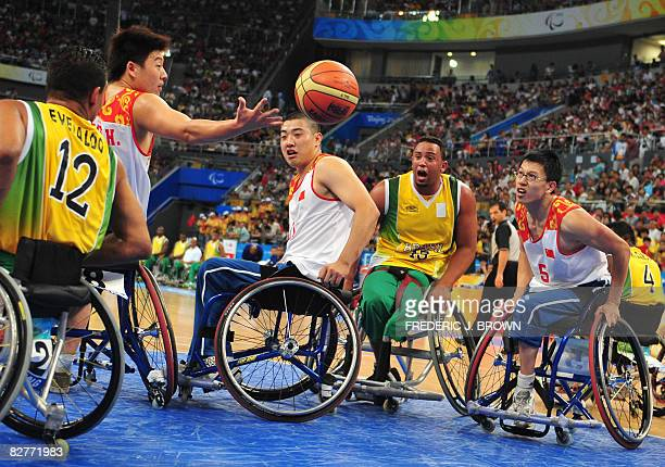 China's Hai Ding Qu Huanjian and Huang Xunan rebound with Brazil's Everaldo Lima and Leandro Mirando in their men's wheelchair basketball game at the...