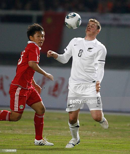China's Hao Junmen tussles for the ball against New Zealand's Chris Wood during a friendly football match in Wuhan central China's Hubei province on...