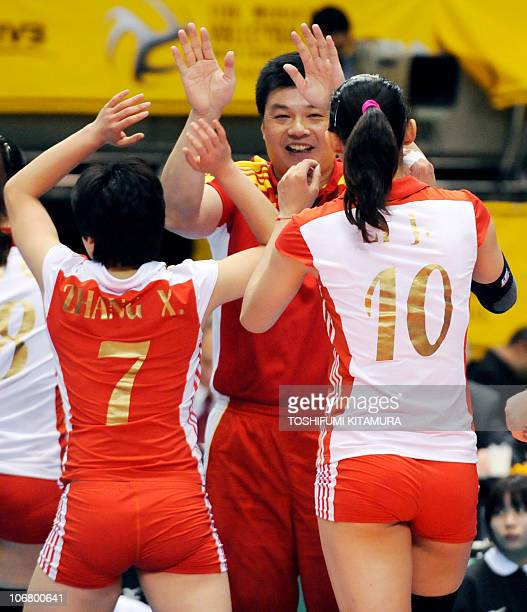 China's head coach Yu Juemin celebrates the victory over Cuba with his players Zhang Xian and Li Juan during their final round/Place 9th12th match at...