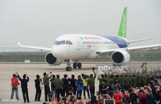 China's homegrown C919 passenger jet returns after completing its maiden flight at Pudong International Airport in Shanghai on May 5 2017 The first...