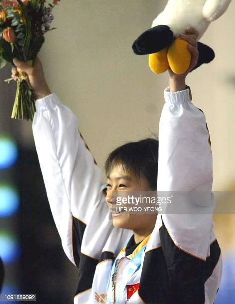 China's Lao Li Shi celebrates with her gold medal during the award ceremony for the women's 10m platform diving final at the 14th Asian Games in...