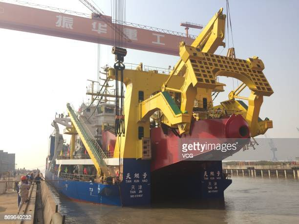 China's largest cuttersuction dredger Tiankun takes water on November 3 2017 in Qidong Jiangsu Province of China Measuring 140 meters long the vessel...