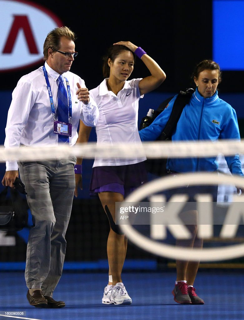 China's Li Na (C) receives medical attention after falling during her women's singles final against Belarus's Victoria Azarenka on the thirteenth day of the Australian Open tennis tournament in Mel...