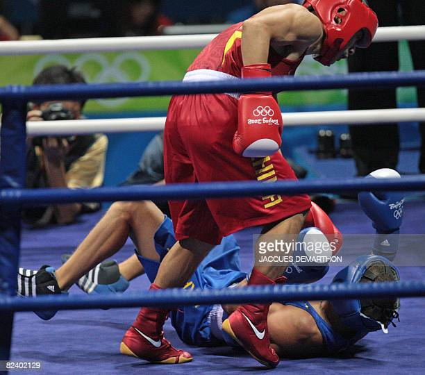 China's Li Yang stands before the fallen Ukraine's Vasyl Lomachenko during their 2008 Olympic Games Featherweight quarterfinals boxing match on...