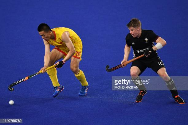 China's Lin Changliang fights for the ball with Wales' Rhodri Furlong during the match between China and Wales at the FIH Mens Series Finals a...