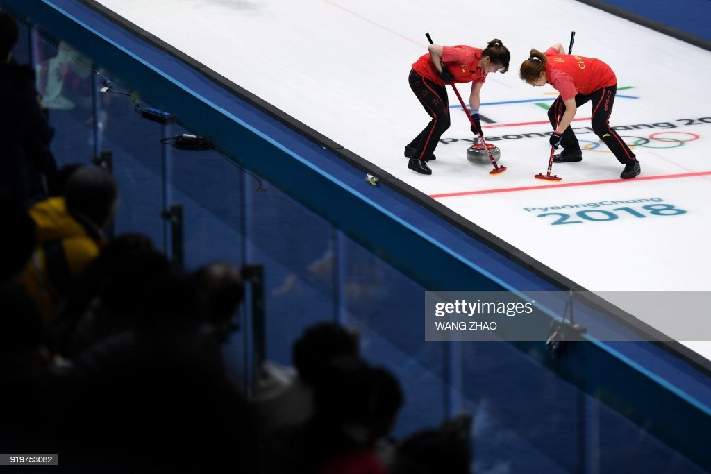 China's Liu Jinli (R) and her teammate brush in front of the stone during the curling women's round robin session between China and South Korea during the Pyeongchang 2018 Winter Olympic Games at the Gangneung Curling Centre in Gangneung on February 18, 2018. / AFP PHOTO / WANG Zhao