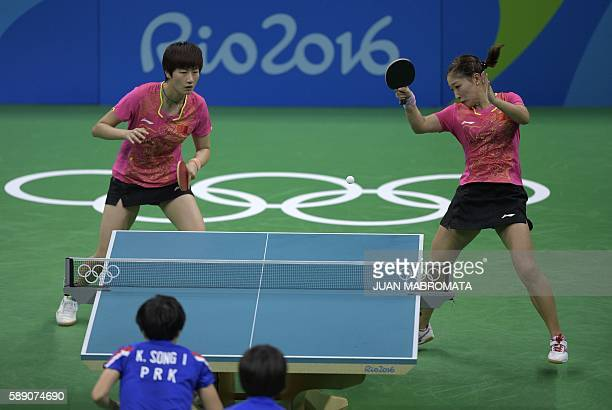 China's Liu Shiwen hits a shot next to China's Ding Ning in their women's team quarterfinal table tennis match against North Korea's Ri Myong Sun and...
