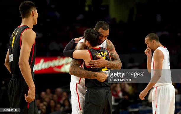 China's Liu Wei and Puerto Rico's Peter John Ramos embrace before the Global Community Cup basketball exhibition game between Puerto Rico and China...